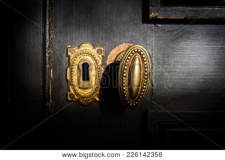 Front View Detail Of Vintage Antique Golden Door Know With Metallic Carvings And Keyhole On Dark Bac