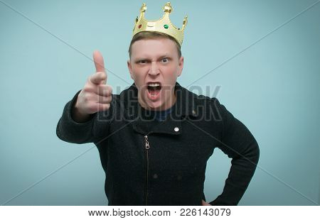 Arrogant  Man With Golden Crown Above His Head Is Yelling Isolated On Blue Background. Wicked And Ar