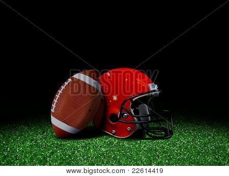 American football and helmet on field over black poster