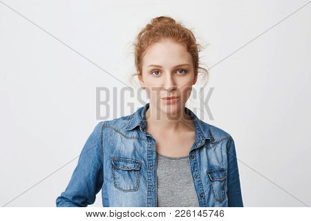 Calm Serious Caucasian Ginger Girl With Hair Combed In Bun, Expressing Irritation Or Indifference Wh
