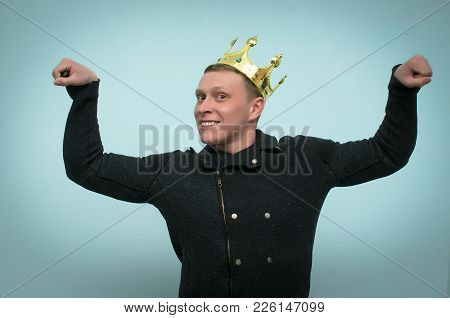 Successful Smiling Man With Gold Crown On His Head Is Showing Muscles On Blue Background. The Winner