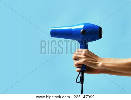 Woman Hands Hold Blue Hair Dryer On Light Blue Background