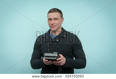 Cheerful Man Is Holding In His Hands A Phone Isolated On Blue Background. Contact Us. Call Us. Custo