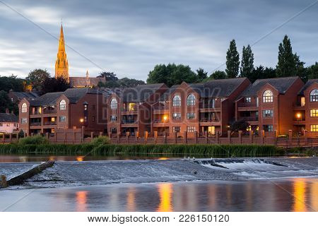 Evening View Of The City Of Exeter. The River Exe And Houses Near The Shore. A Church Is Seen Suspen
