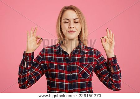 Positive Concentrated Female Keeps Hands In Mudra Gesture, Closes Eyes, Tries To Relax For Minute, I