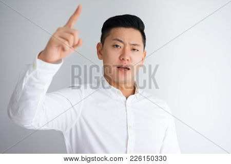 Angry Young Asian Man Wagging Finger At Camera. Boss Scolding Employee. Business And Management Conc