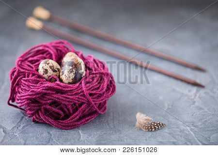Quail Eggs In A Violet Colorful Wool Nest With Knitting Needles. Knitters Easter Postcard Concept. W