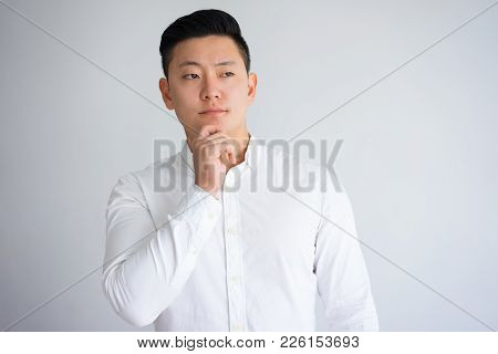 Pensive Asian Man Keeping Touching Chin With Hand. Young Serious Businessman Thinking Over Challenge