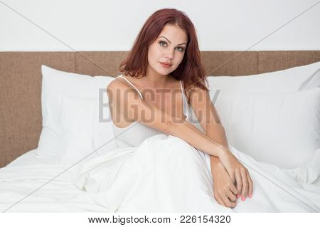 Serious Young Woman Sitting In Bed And Looking At Camera. Calm Beautiful Girl Under Duvet Waking Up