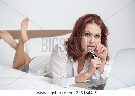 Thoughtful Sexy Woman Working At Home And Looking At Camera. Pensive Attractive Freelancer Using Lap