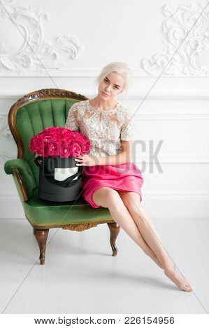 Young Pretty Girl With Cute Face And Long Blond Hair. Woman Standing And Holding Black Box With Red