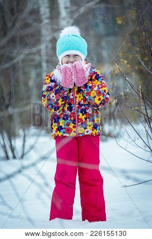 A Child In The Winter In The Park, Playing Snowballs, Leaned His Hands In Mittens To The Face