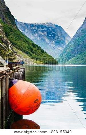 Pier With Red Buoy Ball, Norway Fjord And Mountains In Background. Idyllic Scandinavia