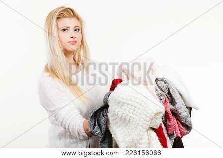 Fashion, Clothes Dilemmas Concept. Woman Holding Big Pile Of Warm Winter Clothing, Cant Decide What