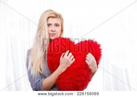 Break Up, Divorce, Bad Relationship Concept. Sad, Depressed Woman Holding Big Red Fluffy Pillow In H