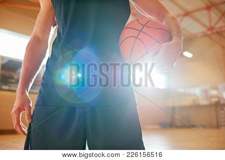 Close-up Of Unrecognizable Basketball Player In Uniform Holding Ball In Sunlight While Standing On I