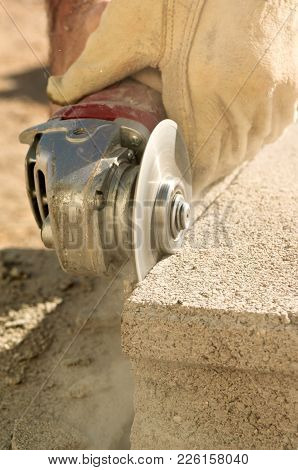 A Closeup Shot Of A Grinding Tool Cutting Into The Edge Of A Cement Block.