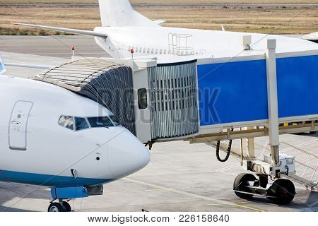 Jetway Is Served To Passenger Airplane At Airport. Close Up. Preparation For Departure, Boarding Pas
