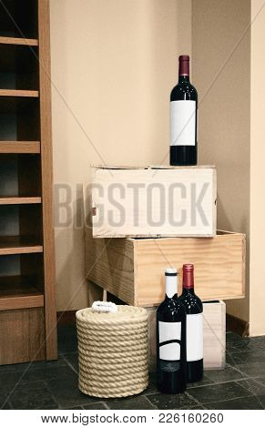 Red wine bottles Three bottles of red wine are standing on wooden crates in the wine cellar Vertical photo template in beige tones