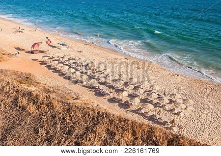 Sunbeds And Umbrellas On The Falesia Beach In Afternoon Sun, Algarve, Portugal
