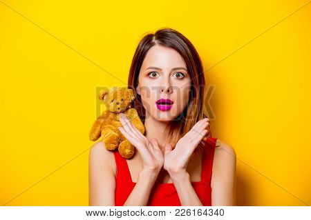 Girl In Red Dress With Teddy Bear Toy On Her Shoulder