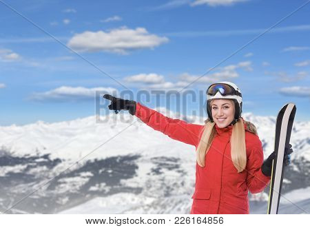 Skier On The Background Of Snow-capped Mountains. Attractive Blonde In A Red Ski Suit With Snowboard