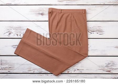 Female Beige Trousers, Top View. Women Formal Pants On White Wooden Background. Female Classic Outfi