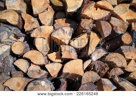 Pile Of Chopped Fire Wood Prepared For Winter. Old Firewood Pile Background