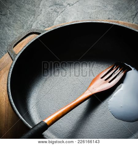 A Black Cast-iron Frying Pan For Cooking Food. Vegetable Oil With Spices. Copy Space.
