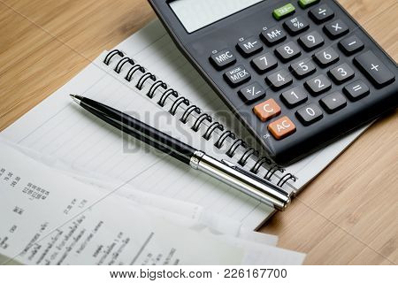 Bill Payment Or Cost Calculation Concept, Black Pen On Paper Notepad With Pile Of Bills And Calculat