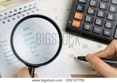 Personal Expense Calculation Or Pay Day Concept, Magnifying Glass On List Of Numbers Of Expenses Wit