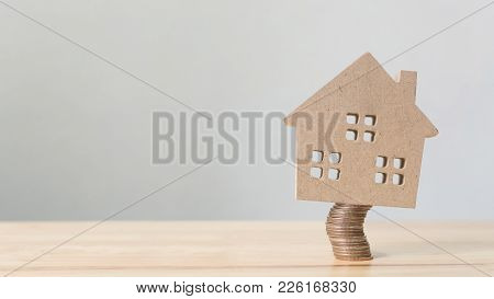 Property Investment And House Mortgage Financial. Risk Management Concept. Wooden Home On Coins Stac