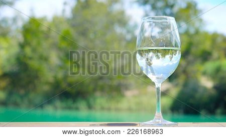 Glass Of White Wine On Outdoor Verandar Rail, With Reflections Of Australian Country Setting, Baross