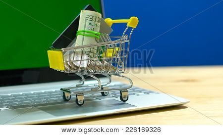 E-commerce Retail Shopping Concept With Miniature Shopping Cart And Modern Laptop Against Chroma Key