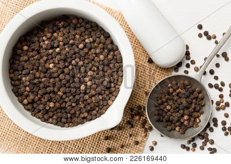 Raw, Natural, Unprocessed Black Pepper Peppercorns In Mortar And Metal Spoon On White Wooden Table