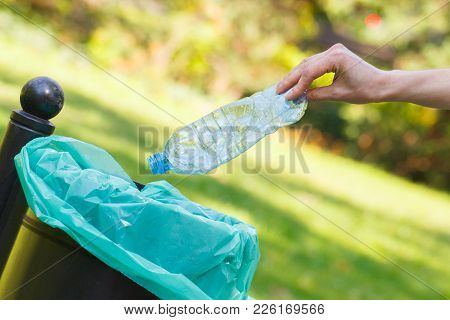 Hand Throwing Plastic Bottle Into Old Trash Can, Concept Of Environmental Protection, Littering Of E