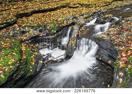 Whitewater Splashes Through Rocky Ledges Scattered With Colorful Fallen Autumn Leaves In Watkins Gle