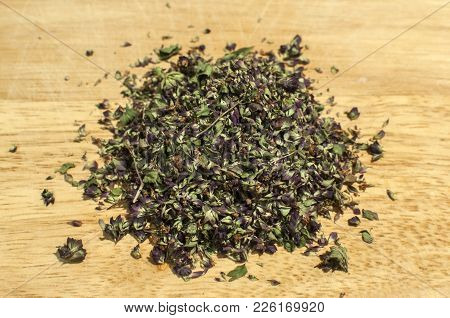 Pile Of Crushed Dried Oregano To Spice Up Dishes Closeup On Wooden Board Background