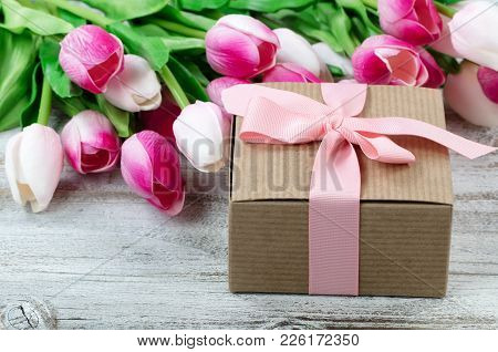 Close Up View Of A Brown Gift Box With Pink Tulips In Background On White Weathered Wooden Boards