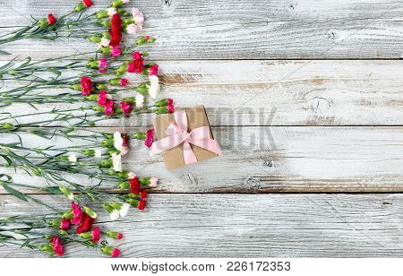 Colorful Carnations And Gift Forming Left Border On White Weathered Wooden Boards