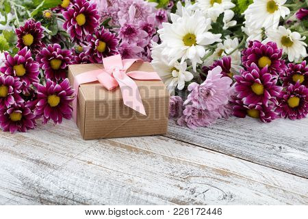 Gift Box With Colorful Mixed Flowers In Background On White Weathered Wooden Boards