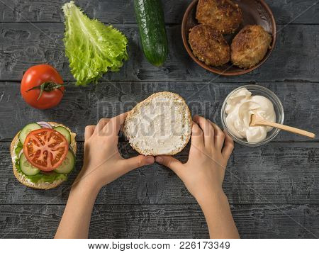 The Girl Holds In Her Hands The Other Half Of The Hamburger Bun. Cooking Hamburger For School Lunch