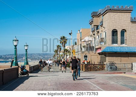 San Diego, California - February 9, 2018:  People Ride Bikes On The Mission Beach Boardwalk, A Concr