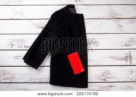 Female Black Overcoat And Red Purse. Ladies Elegant Cloak And Red Leather Wallet, White Wooden Backg