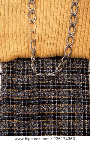 Close Up Female Sweater And Skirt. Detail Of Beige Sweater And Dark Skirt. Women Clothes And Chain.
