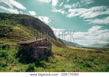 Wide-angle Shooting Of Wooden Desolate Hut Surrounded By Mountains, Hills Recedes Into The Distance