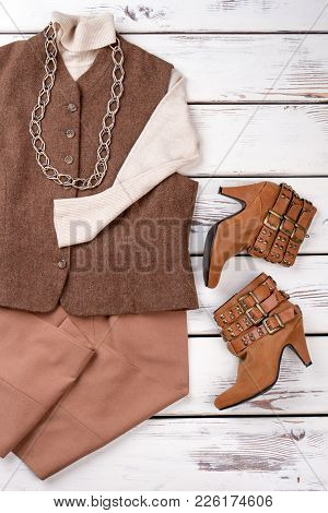 Set Of Elegant Female Clothes. Women Vest And Sweater. Female Trousers And Boots On Vintage Wooden B