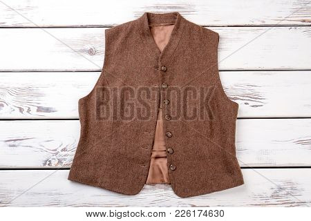Female Brown Vest, Top View. Women Woolen Buttoned Waistcoat On White Wooden Background. Female Clas