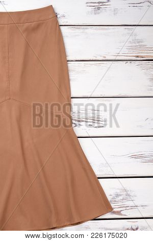 Long Brown Skirt, Wooden Background. Female Skirt On White Wooden Table, Copy Space.