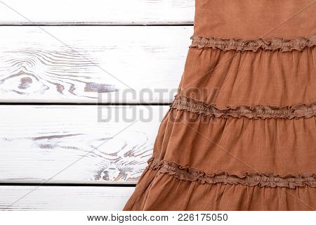 Babycord Brown Skirt, Wooden Background. Vintage Skirt On White Wooden Table, Space For Text.